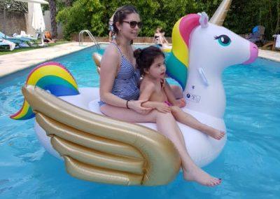 Photo de la piscine : jeune femme et petite fille sur une grosse bouée en forme de licorne.